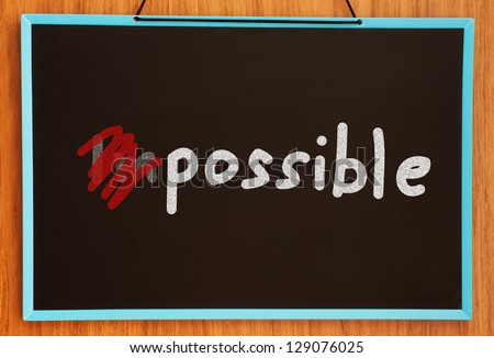 word impossible turning into possible on chalkboard background - stock photo