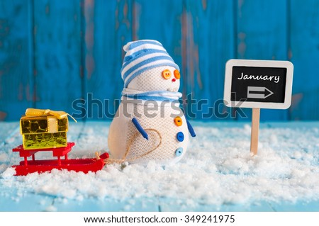 Word January written on direction sign and Snowman with red sled and new year gift. New Year decorations - stock photo