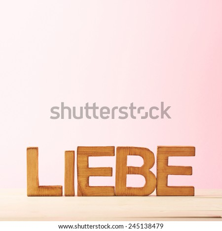 Word Liebe meaning Love in German language as a composition of wooden block letters against the pink background - stock photo