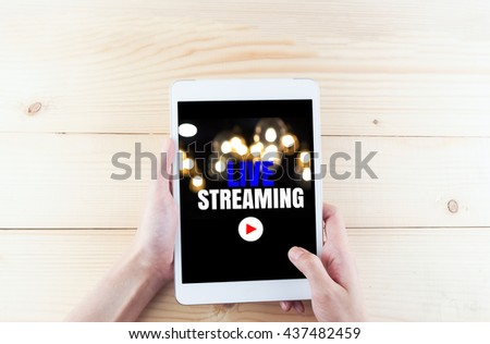 word live streaming on tablet in hand on wooden desk