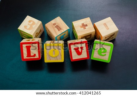 Word 'love' from wooden alphabet blocks with letters.