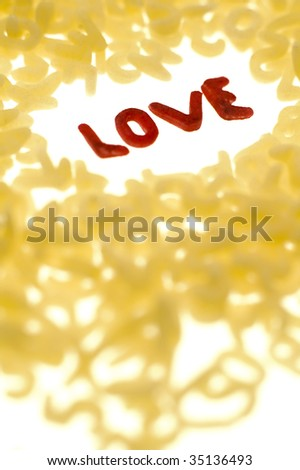 word LOVE in red color made out of food letters, white background