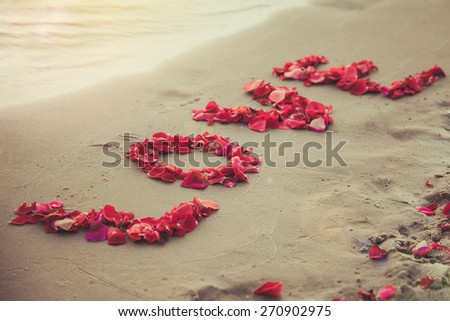 Word love made of red rose petals. Symbol of love. Screen saver for love story. Background for text about wedding and wedding trips. Flower petals in the shape of the word love on the sand beach. - stock photo
