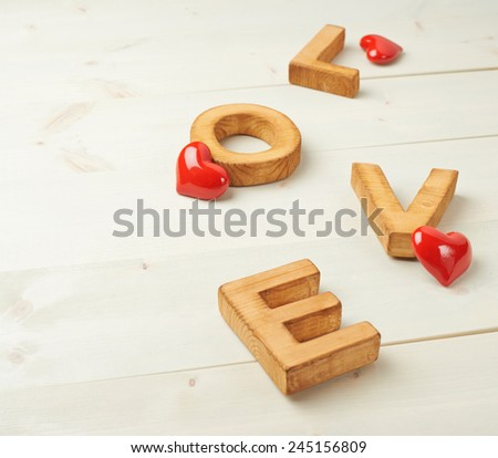 Word Love made with block letters over the wooden surface next to few glossy red hearts as a Valentine's Day love composition, background - stock photo