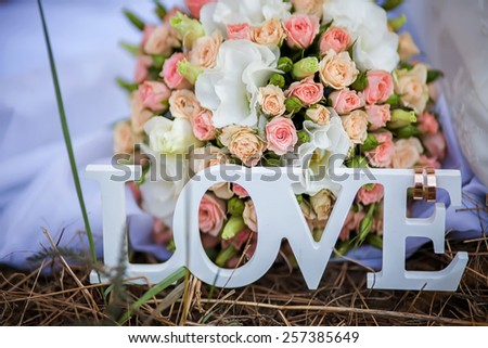 Word Love made with white  letters over the wooden surface next to the bouquet of flowers as a Valentine's Day love or Wedding composition, background - stock photo