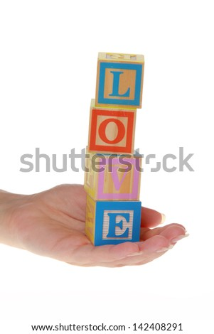 "Word ""love"" of children's blocks holding adult hand on isolated white"