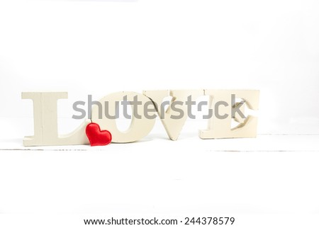 Word love with heart shaped on white wooden background. Valentines Day background - stock photo