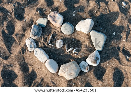 Word love written with pebbles and symbol of heart on the beach sand