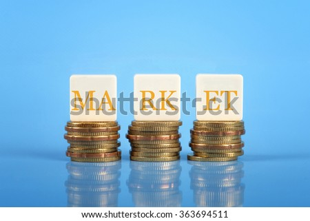Word MARKET on stacked coins, finance conceptual.