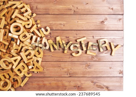 Word mystery made with block wooden letters next to a pile of other letters over the wooden board surface composition