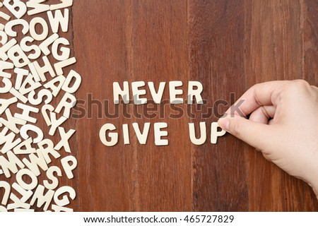 Word never give up made with block wooden letters next to a pile of other letters over the wooden board surface composition