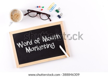 Word of Mouth Marketing word on chalkboard with coffee cup and eyeglasses, view from above - stock photo