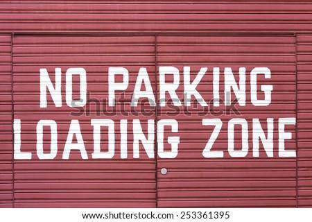 Word of No parking loading zone on metal red door  - stock photo