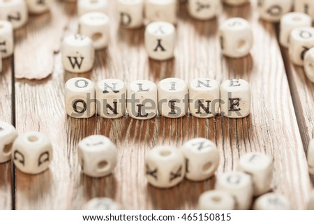 Word ONLINE letters on old wooden board background.