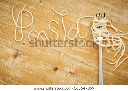 Word pasta made of cooked spaghetti with fork on wooden background - stock photo