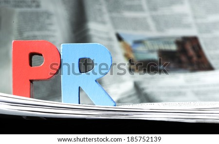 Word PR on newspaper. Wooden letters - stock photo