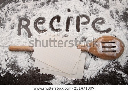 Word recipe written in white flour and spatula on wooden table - stock photo