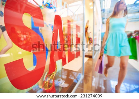 Word �¢??sale�¢?? on shop window and female shopper with paperbags walking on background - stock photo