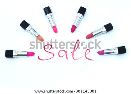 """Word """"sale"""", written with red lipstick, and six different lipsticks around - stock photo"""