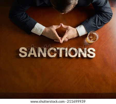 Word Sanctions made of wooden block letters and devastated middle aged caucasian man in a black suit sitting at the table with the glass of whiskey, top view composition with dramatic lighting - stock photo