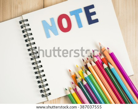 "Word spell ""Note"" and colorful pencil on blank notebook with pen on wood background (Business concept) - stock photo"
