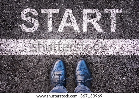 Word Start written on an asphalt road with legs and shoes - stock photo