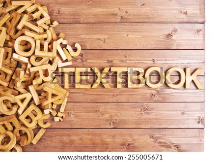 Word textbook made with block wooden letters next to a pile of other letters over the wooden board surface composition - stock photo
