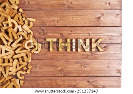 Word think made with block wooden letters next to a pile of other letters over the wooden board surface composition - stock photo