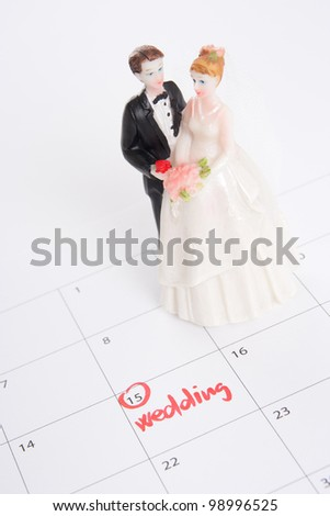 Word wedding in calendar and wedding figurines - planning a wedding concept - stock photo