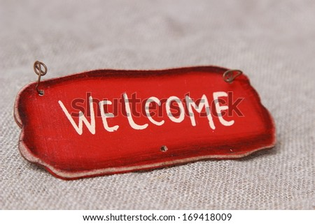 word welcome over canvas background/Welcome sign on wooden fence - stock photo