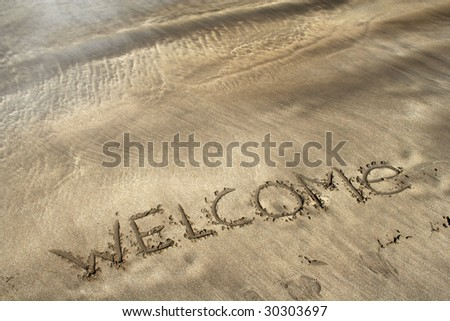 word welcome written on the sea beach - stock photo