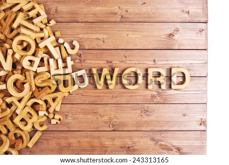 Word word made with block wooden letters next to a pile of other letters over the wooden board surface composition - stock photo