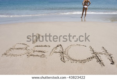 word written in sand on beautiful tropical beach with shapely woman in white bikini standing behind with hands on hips looking out over water