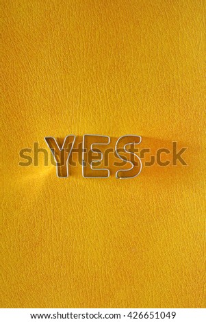 word YES formed with rotary cutters on yellow leather background