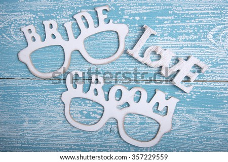 Words BRIDE, GROOM and LOVE on old wooden background - stock photo
