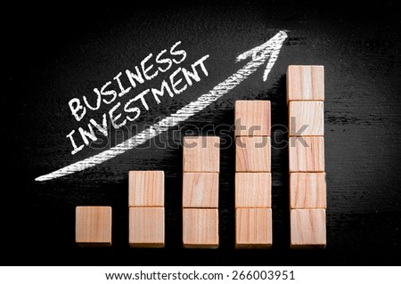 Words Business Investment on ascending arrow above bar graph of Wooden small cubes isolated on black background. Chalk drawing on blackboard. Business Concept image. - stock photo
