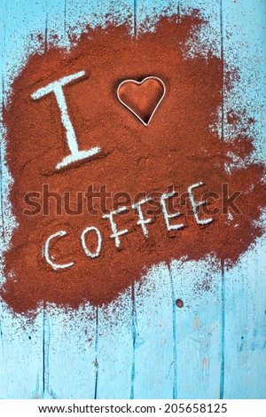 Words i love coffee written on ground coffee, coffee powder on blue wooden table  - stock photo