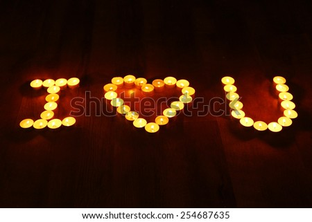 Words I LOVE YOU formed by burning candles on dark background - stock photo