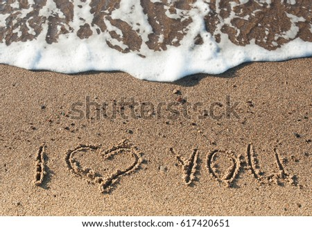 "Words ""I Love You"" written on sand with white foam on background"