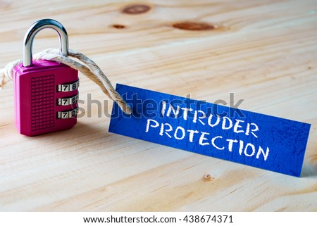 Words INTRUDER PROTECTION written on tag label tied with a padlock. - stock photo