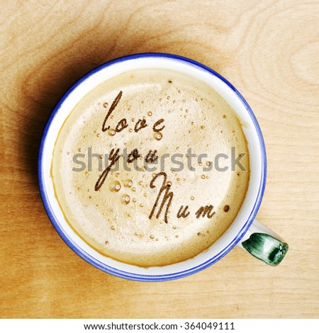 Words love you mum formed from coffee foam. Cup of cappuccino coffee on wooden table. Mothers Day. - stock photo