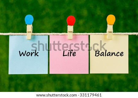 Words of Work Life Balance on sticky color papers hanging by a rope against blurred green background. - stock photo