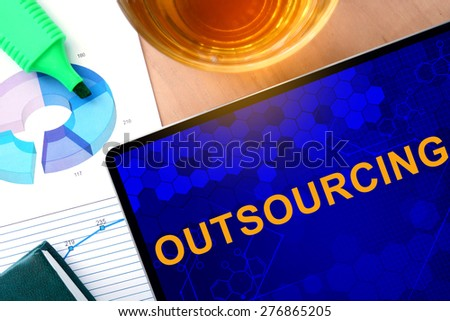 Words Outsourcing  on the tablet and charts.