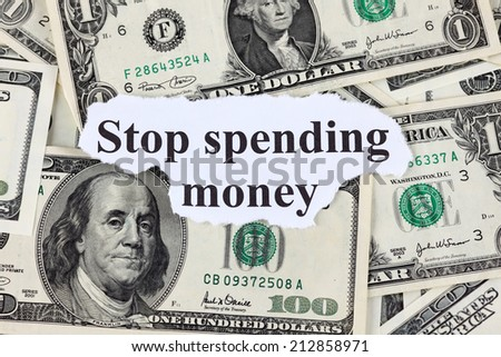 "Words ""Stop spending money"" and dollar bills. Close-up. - stock photo"