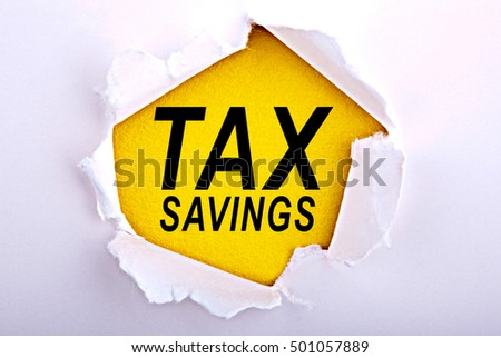 Words Tax savings on ripped paper - Business, technology, internet concept. Stock Photo
