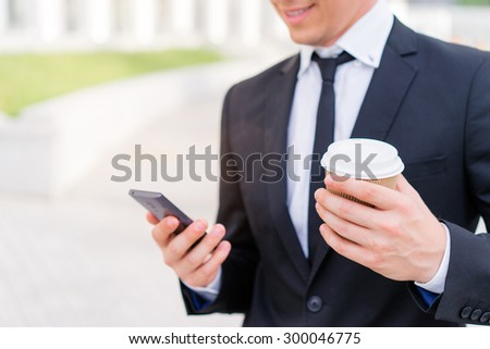 Work and coffee break. Cheerful young businessman using smartphone and holding cup of beverage. - stock photo