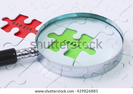 WORK AND  EXCUSE puzzle with magnifier glass - stock photo