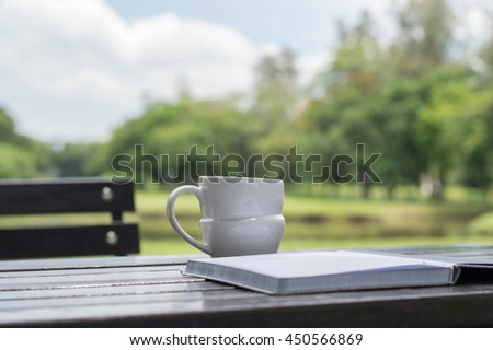 Work at park backgrounds concept. Coffee cup with book on wooden table under the spring sunlight in a park. Using as background or wallpaper