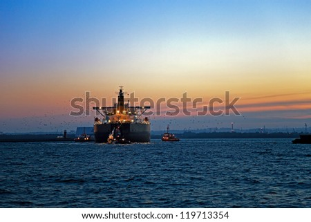 Work at sea after sunset - a cargo ship enters the port, escorted by tugboats.