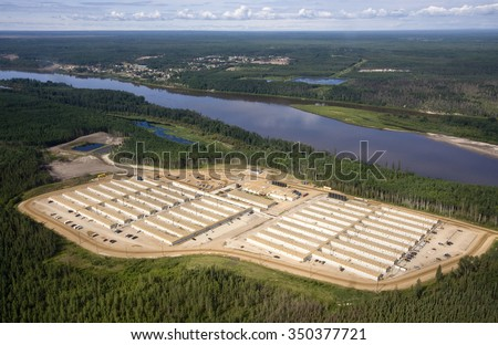 Work camp for oil sands workers along the Athabasca River, north of Fort McMurray, Alberta. Hamlet of Fort McKay on far side of river.  July 10, 2014. - stock photo